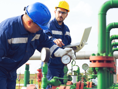 Oil gas measurement personnel reviewing measurements in the field by gas certification institute in houston texas.